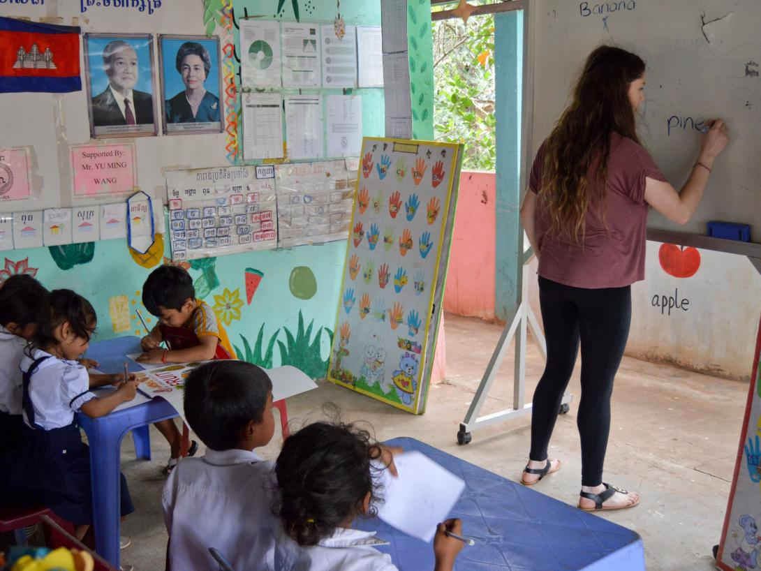 A care volunteer in Cambodia teaches children in a preschool the names of fruits instead of working in an orphanage.